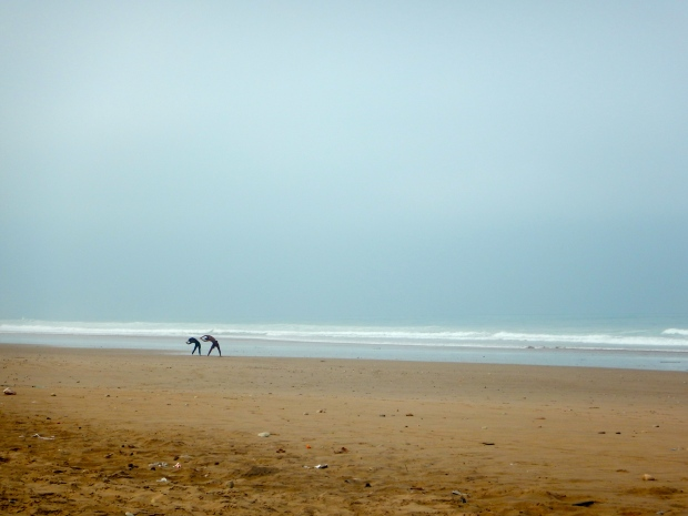 Some surfers doing some warm-up stretches on a deserted beach